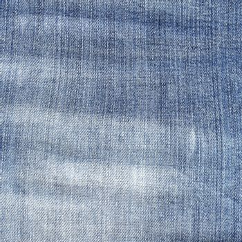 Shabby blue jeans texture. Light torn jeans