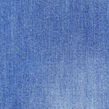 Shabby denim texture. Light blue jeans background.