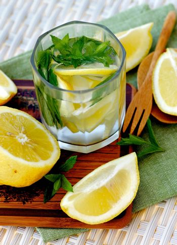 Lemon and Mint Beverage in Glass with Halves of Lemon on Napkin closeup on Wicker background. Focus on Top of Drink