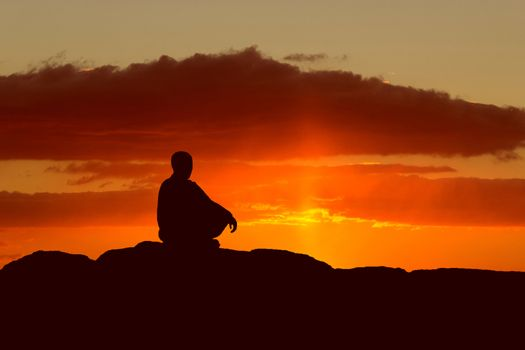 buddhist monk meditating at sunset sitting on a rock by the sea