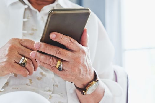 close up image of Senior woman using her mobile phone background.  An idea of modern lifestyle, communication,telecommunication,connectivity, social networking