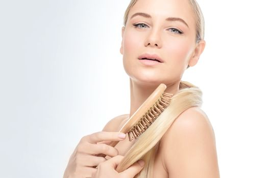 Portrait of a gorgeous woman over clear background combing her blond hair with wooden hairbrush, fashion model wearing natural makeup