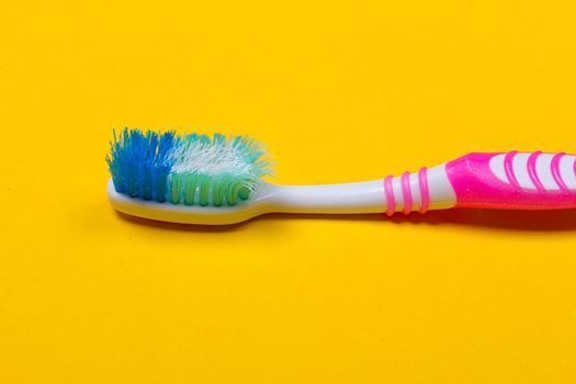 Old used toothbrush on the yellow background. Top view