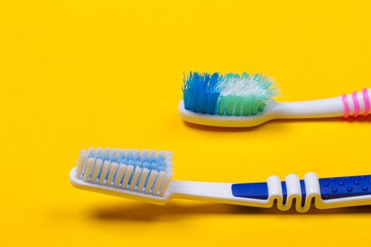 Old used and new toothbrushes on the yellow background. Top view