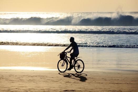 A girl on a bicycle is riding along the ocean at sunset. Bali, Indonesia