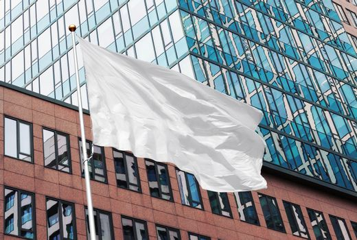 White blank flag waving in the wind in the urban background of modern buildings and skyscrapers. Perfect mockup to add any logo, symbol or sign