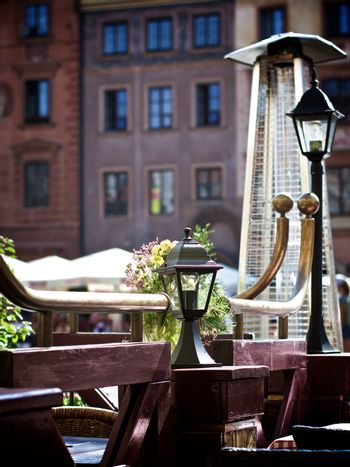 Old Empty Sidewalk Cafe with Wooden Tables, Partitions, Street Lanterns and Heat Stands against Blurred Medieval Houses Outdoors. Warsaw, Poland