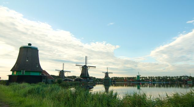 Famous Zaanse Schans Windmills from River Coast with Reflection on Water Early Morning Outdoors