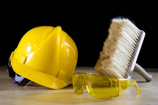Safety glasses, helmet, work gloves and brush. Tools on a wooden table. Black background.