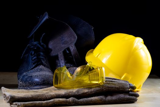 Workwear for a construction worker. Helmet, gloves, shoes and sunglasses on a wooden table. Black background.