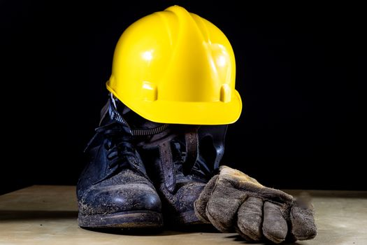 Muddy working boots with helmet and gloves. Accessories for the worker. Black background.