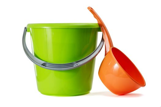 The green plastic bucket and red ladle is isolated on a white background