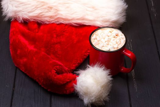 Hot chocolate with marshmallows and cap santa on grunge dark table