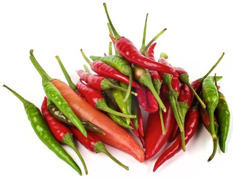 Stack of Various Perfect Red, Orange and Green Hot Chili Peppers closeup on White background