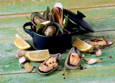Arrangement of Fresh Boiled Green Mussels with Spices and Lemon in Dark Pannikin closeup on Green Wooden background