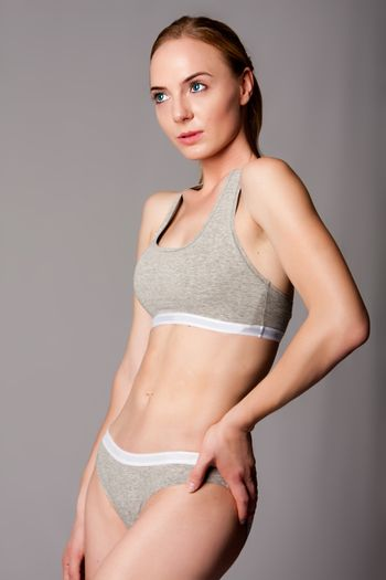 Beautiful attractive young woman in grey sports underwear with bra and panties showing abdomen.
