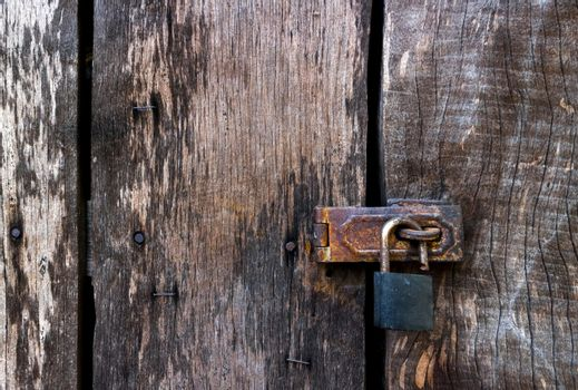 Old master key lock on old wooden background