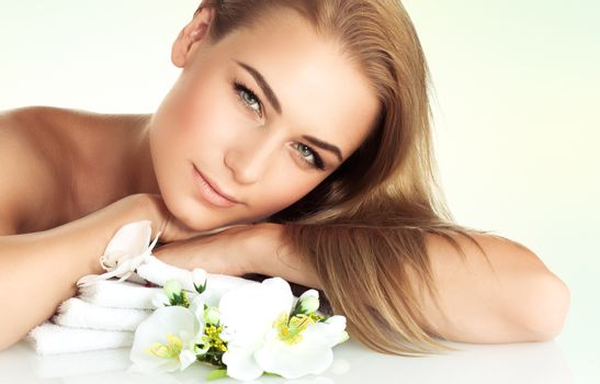 Portrait of a gentle girl relaxing at spa salon, enjoying day spa on the massage table with tender white orchid flowers aroma, healthy lifestyle