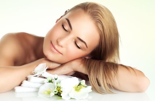 Portrait of a nice gentle girl with closed eyes of pleasure relaxing at spa salon, enjoying day spa on the massage table with tender white orchid flowers aroma, healthy lifestyle concept