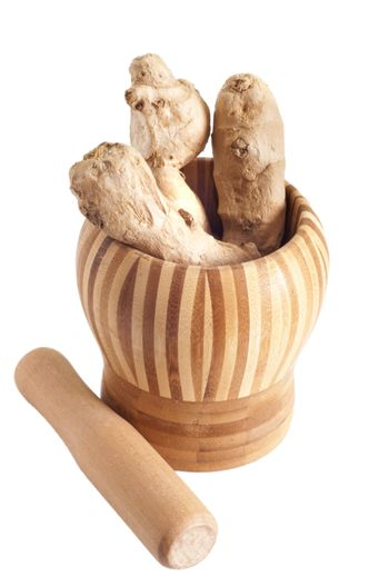 a pieces of ginger inside bamboo mortar