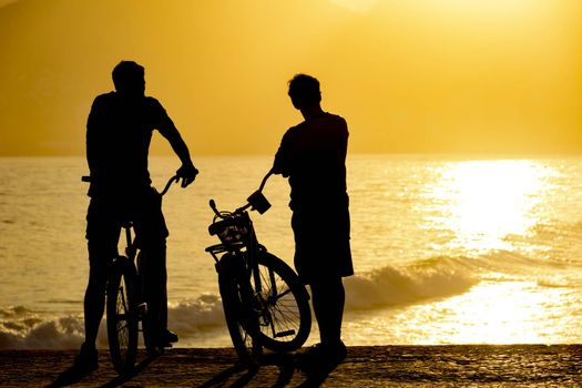 Two cyclists during the late afternoon on the seafront watching the sunset