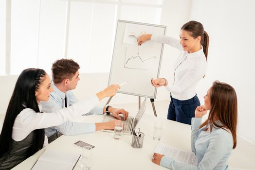 Businesspeople having meeting in a office. Young businesswoman standing  in front of flip chart and having presentation.