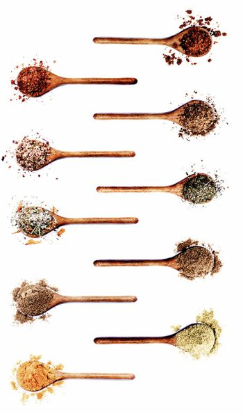 Collection of Various Spices in Wooden Spoons: Dried Paprika, Dried Chili, Salt with Chili, Salt with Cayenne Pepper, Coriander, Salt with Petals, Cumin Powder, Thyme, Zira and Curry Powder on White background