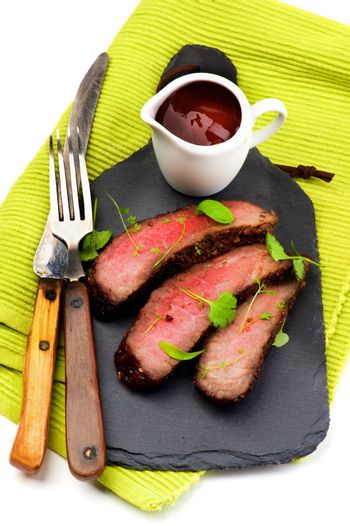 Slices of Roast Beef Medium Rare on Slate Serving Board with Tomato Sauce, Fork and Table Knife on Green Napkin closeup