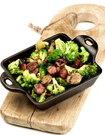 Homemade Useful Stew with Broccoli and Grilled Sausages in Black Iron Cast on Wooden Board on White background
