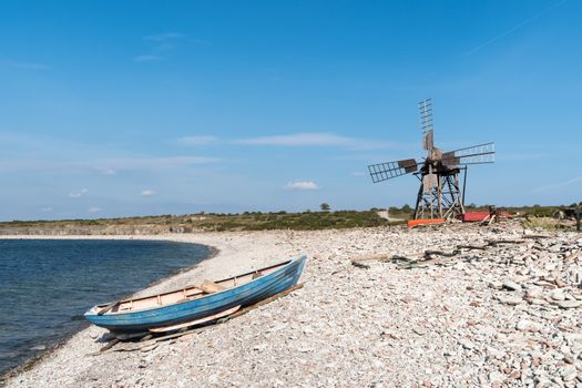 Blue rowing boat and an old windmill by seaside