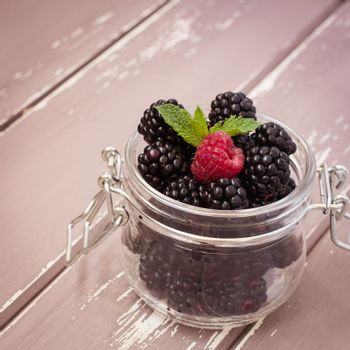 Red raspberries and blackberries in a glass jar with a leaf of mint, 1x1 size