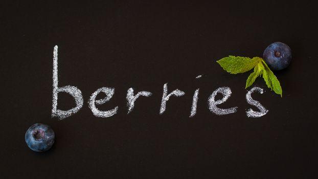 Berries in English on the blackboard, flat lay