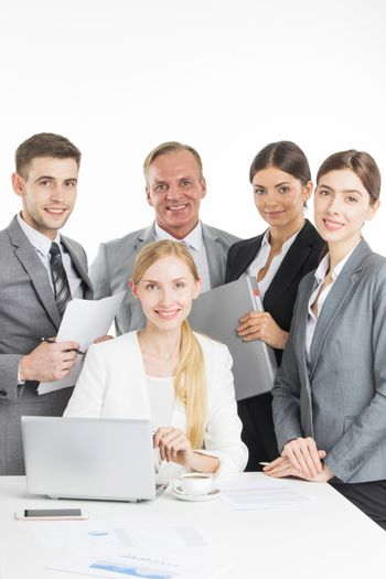 Smiling business people team working together with papers isolated on white background