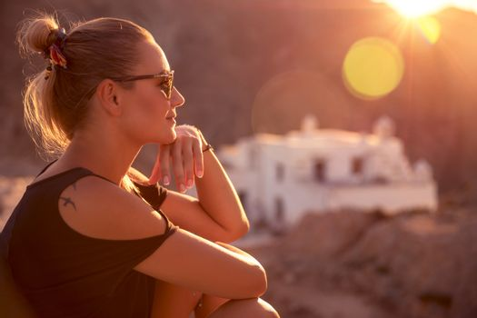 Beautiful woman enjoying spiritual travel to the wonderful place, sunset light scene, sitting on the mountains near the monastery, happy summer holidays