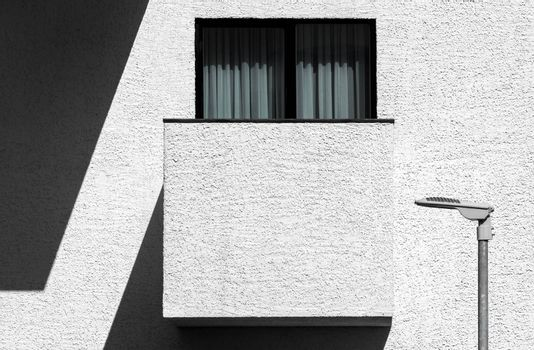Abstract modern minimalist architecture with balcony, window and street lamp. High contrast outdoor facade picture