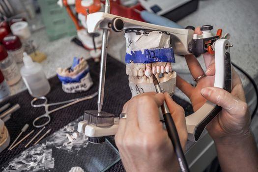Dental technician painting denture
