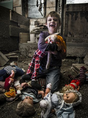 Creepy boy and scary clown doll in the barn