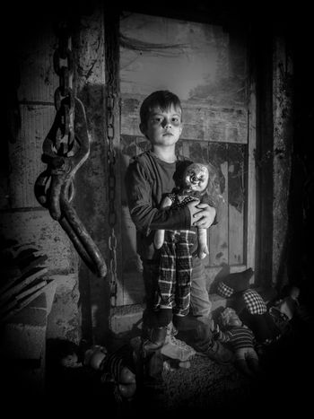 Creepy kid and scary clown doll in the barn