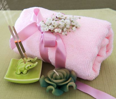 a pink towel, incense sticks and candle