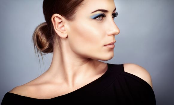 Portrait of a beautiful young woman with stylish makeup over on gray background, profile face, gorgeous fashion look