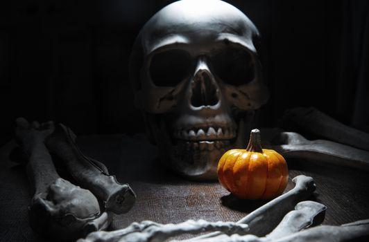 Human bones and skull on the table with Halloween pumpkin