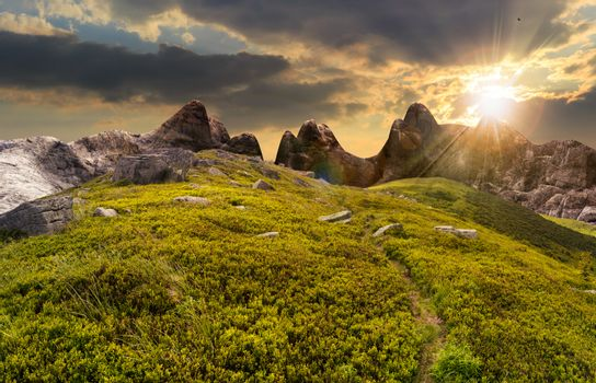 path through boulders on hillside at sunset