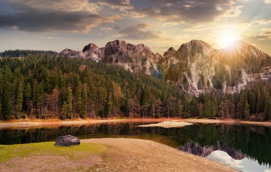 lake near the mountain in pine forest at sunset