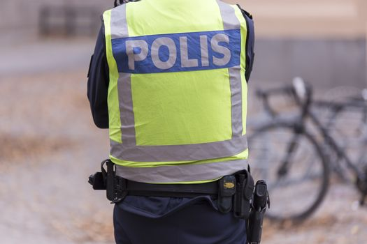 Swedish Police Officer back with gun.