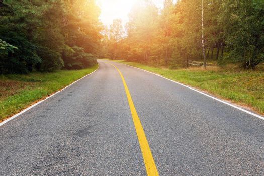 Empty country road with yellow line in the middle at sunset