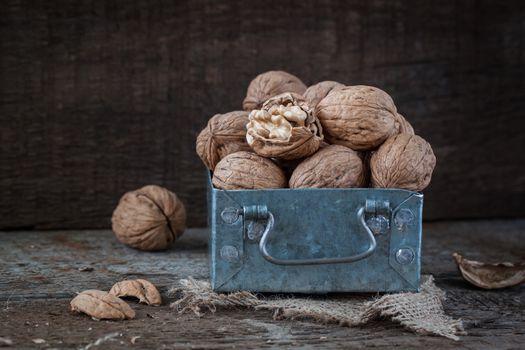 Walnuts in a small iron box and a canvas napkin.