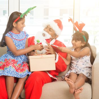 Happy Indian family celebrating Christmas holidays, with gift box and santa claus sitting on sofa or couch at home, Asian people festival mood.