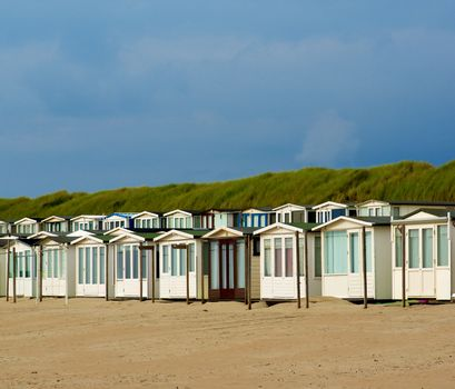 Beach Houses in Dunes on North Sea coast against Blue Sky in Netherlands Outdoors