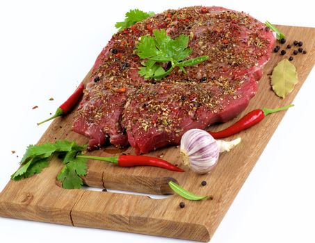 Marinated Raw Boneless Beef Shank with Herbs and Spices, Garlic and Chili Pepper on Wooden Cutting Board closeup on White background