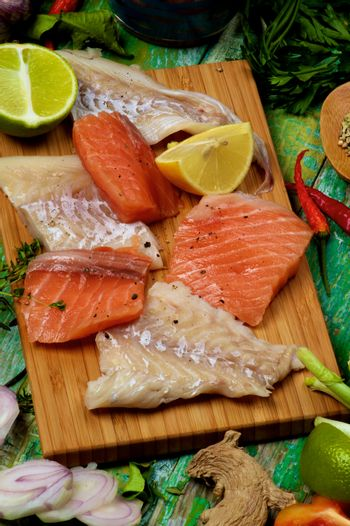Arrangement of Raw Fillet of Salmon and Cod, Greens, Spices and Citrus Fruits closeup on Cracked Wooden background